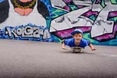 Gullig ung pojke som spelar på hans skateboard Arkivbild