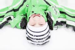 Gullig ung pojke som tycker om den kalla vintersnön Royaltyfria Foton