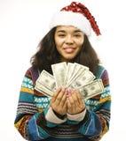 Gullig ung verklig afrikansk flicka i santas den röda hatten med pengarisolat Arkivbilder