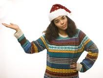 Gullig ung verklig afrikansk hipsterflicka i santas den röda hatten som isoleras på den väntande på vintern Christmass för vit ba Royaltyfria Bilder