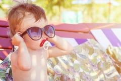 Gullig unge i solglasögon som sitter på en schäslong på den tropiska sandstranden arkivfoton