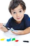 Gullig unge som leker med färger Arkivbild