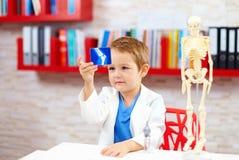 Gullig unge som spelar en doktor som ser röntgenstrålebild av benet Royaltyfri Fotografi