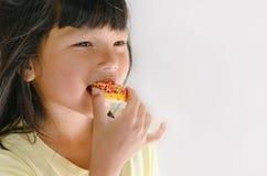 Gullig ungeflicka som sött äter Arkivfoton