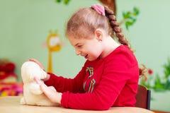Gullig ungeflicka som spelar med den flotta leksaken i dagiset för barn med specialt behov royaltyfri fotografi