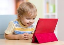 Gullig ungelitet barnpojke med minnestavlaPC royaltyfri bild