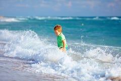 Gullig ungepojke som har gyckel i havsbränning Arkivfoton