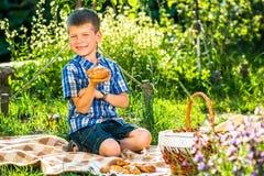 Gullig ungepojke som har picknicken Arkivbild