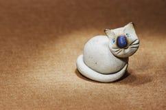 Gullig vit katt för keramisk statyett med blåa ögon Arkivfoto
