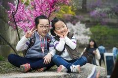 Gulliga älskvärda asiatiska systrar poserar för deras mum under vårtid på parkerar Arkivbilder
