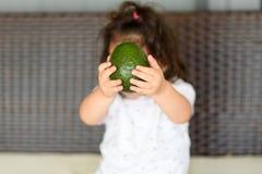Gulliga asiatiska barn eller frukt för avokado för ungeflickainnehav och att sitta på soffan med utrymme royaltyfria bilder