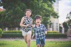 Gulliga asiatiska barn som tillsammans kör Royaltyfria Foton