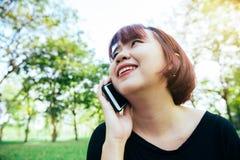 Gulliga asiatiska kvinnaleenden och samtal på mobiltelefonen, medan sitta in parkera vårdagen Arkivbilder