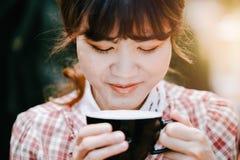 Gulliga asiatiska kvinnor som rymmer leende för kaffekopp, tycker om till att dricka den varma drinken fotografering för bildbyråer