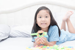 Gulliga asiatiska tegelstenar för flickalekkvarter på säng Arkivfoton