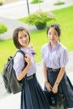 Gulliga asiatiska thailändska höga skolflickastudentpar i skolalikformig Arkivbild