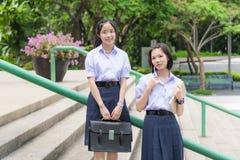 Gulliga asiatiska thailändska höga skolflickastudentpar i skolalikformig royaltyfri fotografi