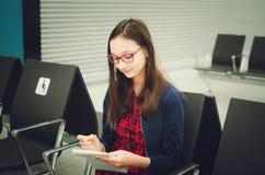 Gulliga bärande exponeringsglas för tonårs- flicka sitter i väntande rum och drar i notepad arkivfoton