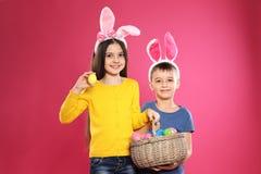 Gulliga barn i kaninörahuvudbindlar som rymmer korgen med påskägg på färg royaltyfri bild