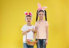 Gulliga barn i kaninörahuvudbindlar som rymmer korgen med påskägg på färg royaltyfri fotografi