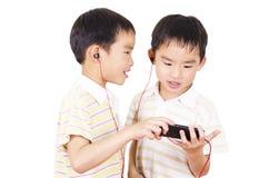 Gulliga barn lyssnar till musik Royaltyfria Foton