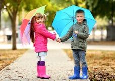 Gulliga barn med paraplyer Arkivbilder