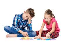 Gulliga barn med stora färgrika alfabetbokstäver på vit bakgrund Begrepp för ungeanförandeterapi Anförandehinder som är logopedy royaltyfri bild