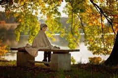 Gulliga barn, pojke som sitter på kanten av en sjö på en solig aut Royaltyfri Bild