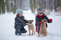 Gulliga barn, pojkebröder som spelar i snön med deras hundkapplöpning Royaltyfri Bild
