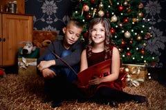 Gulliga barn sjunger en sång på jul Fotografering för Bildbyråer