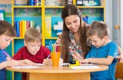Gulliga barn som drar med läraren på förskole- grupp Arkivfoton