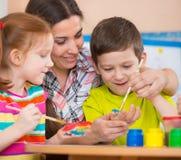 Gulliga barn som drar med läraren på förskole- grupp Arkivbild