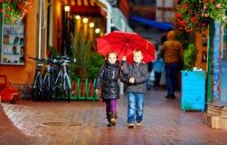 Gulliga barn som går den färgrika aftongatan, under regnet Arkivbild