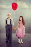 Gulliga barn som går med en röd ballong Fotografering för Bildbyråer
