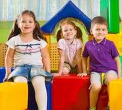 Gulliga barn som spelar i idrottshall Fotografering för Bildbyråer