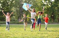 Gulliga barn som spelar med draken utomhus på solig dag arkivbilder