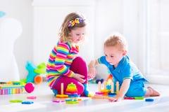 Gulliga barn som spelar med träleksaker Royaltyfri Fotografi