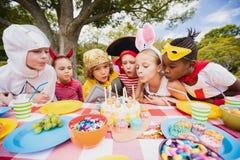 Gulliga barn som tillsammans blåser på stearinljuset under ett födelsedagparti Royaltyfria Foton