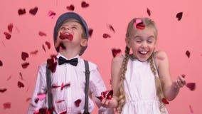 Gulliga barn som tycker om regn från ljusa hjärta-formade konfettier, St-valentindag arkivfilmer