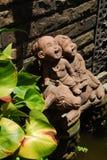 Gulliga barndockor i trädgård Arkivbilder