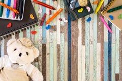 Gulliga björndockor och studenttillbehör på träbakgrund, t arkivfoto