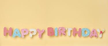 Gulliga bokstäver på guling - lycklig födelsedag, med en trevlig liten shad Arkivfoto