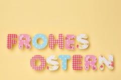 Gulliga bokstäver på guling - tysk: Frohes Ostern: Lycklig påsk, wi royaltyfri foto