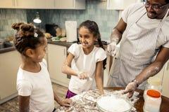 Gulliga döttrar som känner sig fantastiska och gällda, i att laga mat pajen fotografering för bildbyråer