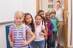 Gulliga elever som ler på kameran i klassrum Royaltyfria Foton