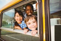 Gulliga elever som ler på kameran i skolbussen Arkivfoto