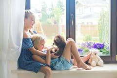 Gulliga europeiska litet barnsystrar som spelar på fönsterbräda nära fönster Royaltyfria Bilder