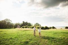 Gulliga försiktiga par som går i den gröna ängen Ung älska familj som tycker om vårtid arkivbild