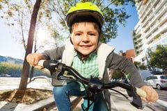 Gulliga fem år gammal pojke som rider hans cykel i stad Royaltyfri Fotografi