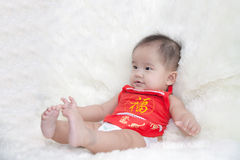 Gulliga fem månader asiat behandla som ett barn att le i röd cheongsam Arkivfoton